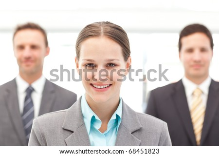 Cheerful businesswoman standing in front of two businessmen at work - stock photo