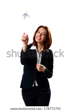 Cheerful businesswoman throwing paper plane isolated on a white background - stock photo
