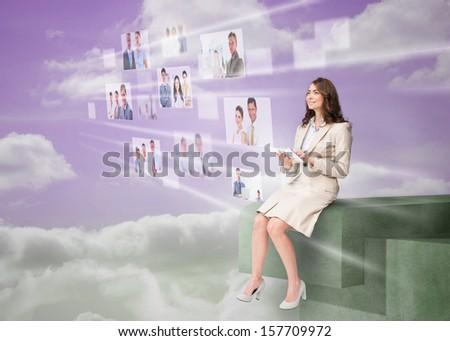 Cheerful businesswoman using futuristic interface while cloud computing - stock photo