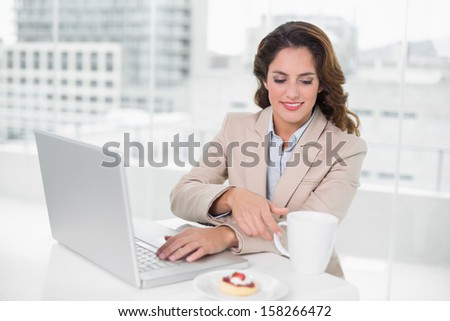Cheerful businesswoman using laptop at her desk and having a coffee in bright office