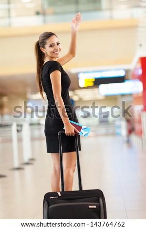cheerful businesswoman waving goodbye at international airport - stock photo