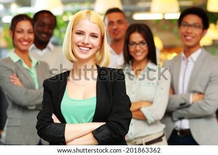 Cheerful businesswoman with arms folded standing in front her colleagues
