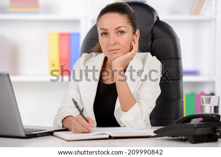 Cheerful businesswomen. Confident middle-aged businesswoman sitting at her working place