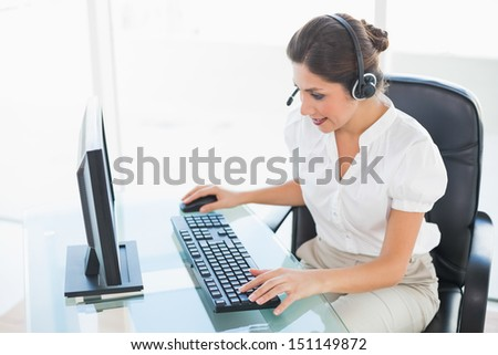 Cheerful call center agent working on computer while on a call in her workplace - stock photo