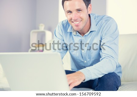 Cheerful casual man using laptop and looking at camera in bright living room - stock photo