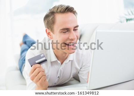 Cheerful casual young man doing online shopping through laptop and credit card on sofa
