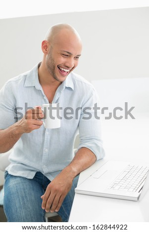 Cheerful casual young man with laptop drinking coffee at home - stock photo
