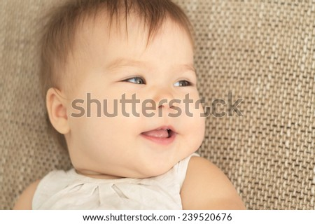 cheerful caucasian baby girl smiling looking away - stock photo
