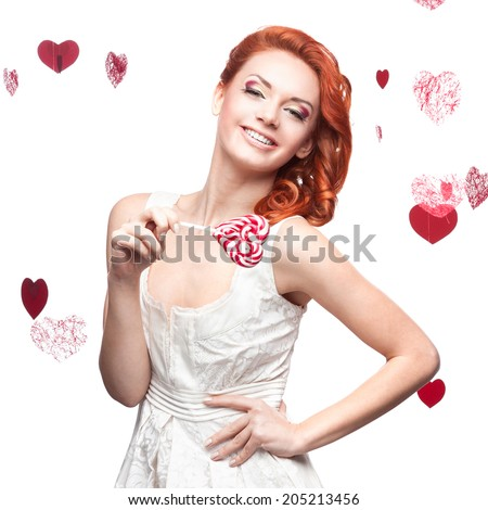 cheerful caucasian red-haired young woman holding lollipop. isolated on white - stock photo