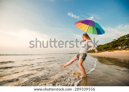 Cheerful caucasian young woman with rainbow umbrella having fun on the Jimbaran beach on Bali before sunset with beautiful ocean and blue sky on background. Travel, holidays, vacation, healthy - stock photo