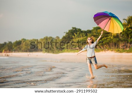 Cheerful caucasian young woman with rainbow umbrella having fun on the Jimbaran beach on Bali before sunset with beautiful ocean and blue sky on background. Travel, holidays, vacation, lifestyle - stock photo