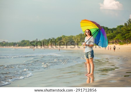 Cheerful caucasian young woman with rainbow umbrella having fun on the Jimbaran beach on Bali before sunset with beautiful ocean and blue sky on background. Travel, holidays, vacation - stock photo