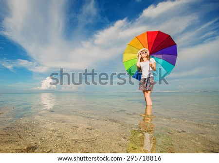 Cheerful caucasian young woman with rainbow umbrella having fun on the Jimbaran beach on Bali with beautiful ocean and blue sky on background