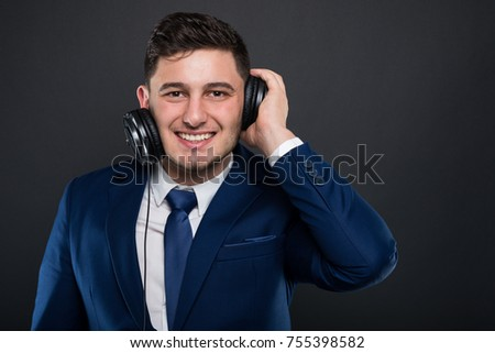 Cheerful ceo posing with modern headphones while listening music in his free time