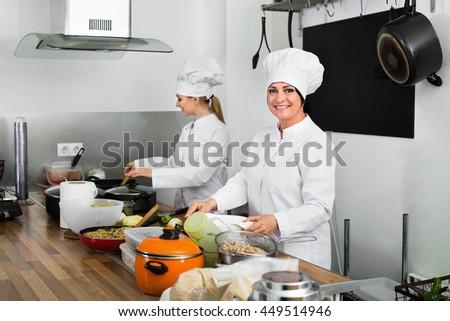 Cheerful charming friendly smiling female chefs preparing food on restaurant kitchen - stock photo