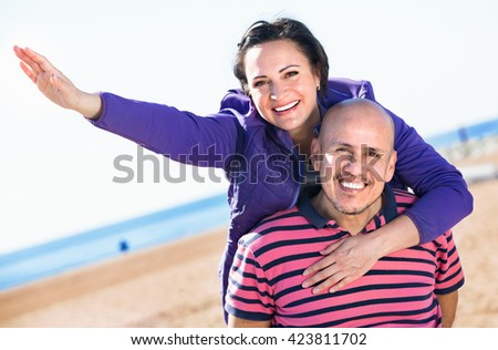 Cheerful  charming mature couple gladly hugging each other and enjoying the beach - stock photo