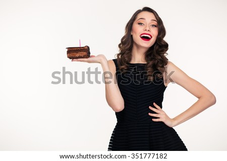 Cheerful charming retro styled young woman holding piece of chocolate birthday cake with candle on the palm over white background - stock photo