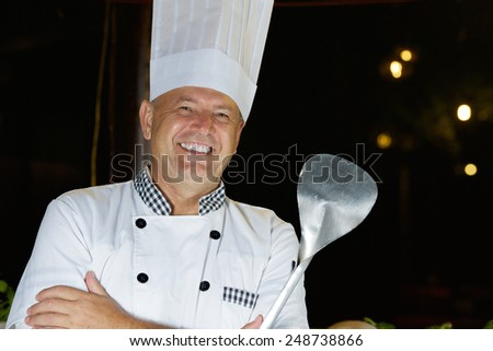 Cheerful chef cook of seafood restaurant invites to barbecue - stock photo
