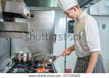 Cheerful Chef frying vegetables in a pan. Young chef preparing a delicious meal in a restaurant kitchen near the stove and watching roasting - stock photo