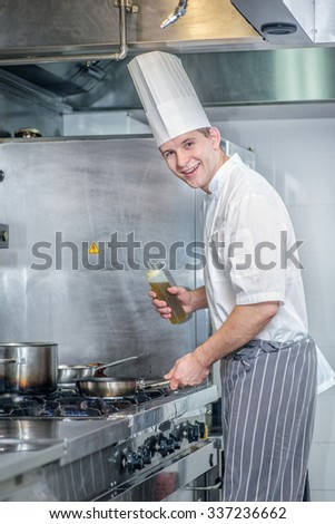 Cheerful Chef prepares to add oil to the pan. Young chef preparing a delicious meal in a restaurant kitchen near the stove and looking at the camera - stock photo