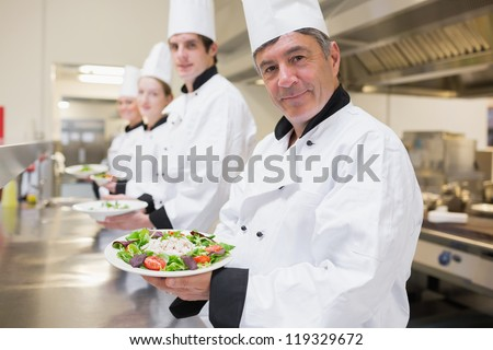 Cheerful Chef's showing their salads in the kitchen