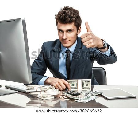 Cheerful chief showing thumbs up success sign / modern businessman at the workplace working with computer - stock photo