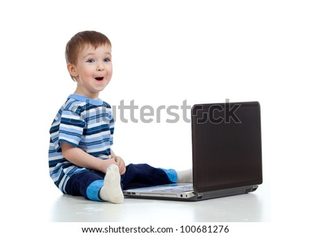 Cheerful child boy using a laptop over white background - stock photo