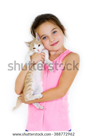 cheerful child girl plays with a little kitten on a light background - stock photo