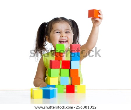 cheerful child girl plays with building blocks and shows red cube - stock photo