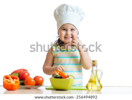cheerful child girl preparing healthy food in the kitchen