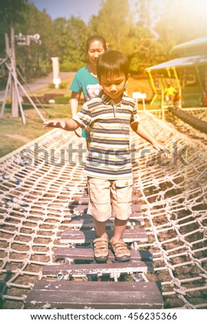 Cheerful child having fun at playground, mother near by. Boy playing at park, outdoors in the day time with bright sunlight. Happy asian family on vacation. Warm tone. - stock photo