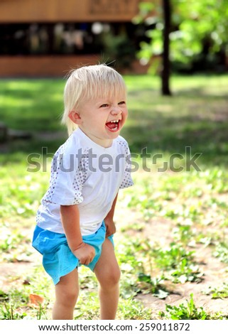 Cheerful Child Laugh at the Summer Park - stock photo