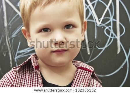 Cheerful child near the blackboard - stock photo