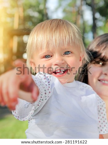 Cheerful Child pointing at You in the Summer Park - stock photo