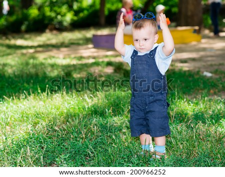 cheerful child with glasses on a walk in the park - stock photo