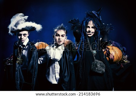 Cheerful children in halloween costumes standing with pumpkins. Over dark background. - stock photo