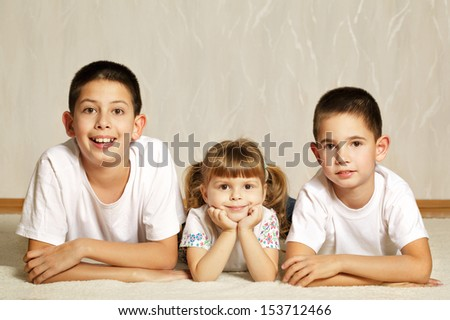 Cheerful children lying on floor together - stock photo
