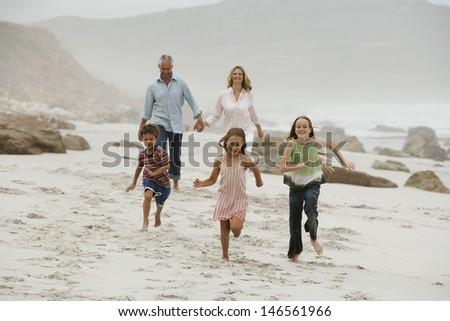 Cheerful children running on beach with parents walking in background - stock photo