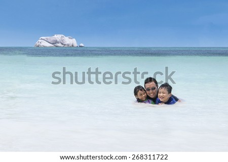 Cheerful children wearing swimsuit and swimming with their father on the beach - stock photo