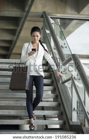 Cheerful Chinese businesswoman reading messages on mobile phone while walking down stairs. - stock photo