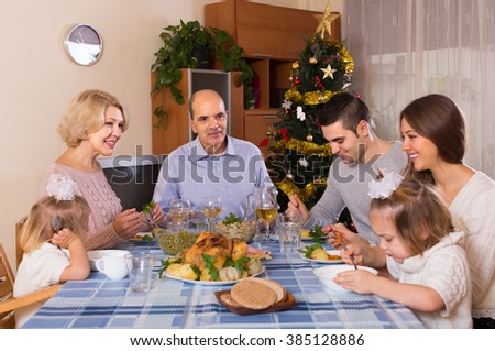 Cheerful christmas celebration in the bosom of family at the table at home - stock photo