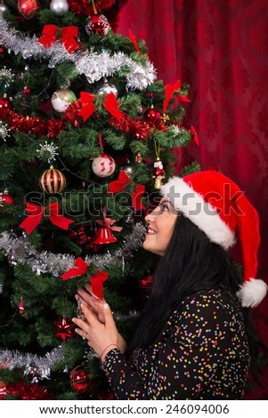 Cheerful Christmas woman looking up to treee and wishing - stock photo