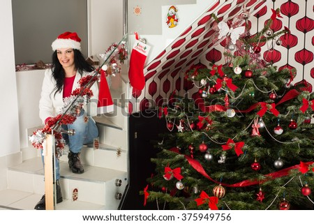 Cheerful Christmas woman sitting on stairs home with natural fir tree - stock photo