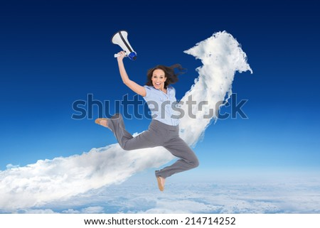 Cheerful classy businesswoman jumping while holding megaphone against cloud arrow - stock photo