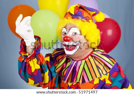 Cheerful clown snaps his fingers in front of festive balloon background.