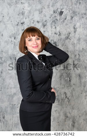Cheerful confident business woman over grunge gray background with copyspace for your text - stock photo