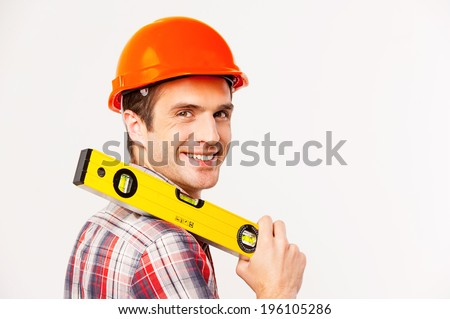Cheerful construction worker. Rear view of handsome young handyman with carrying work tool on shoulder and looking over shoulder while standing against grey background - stock photo