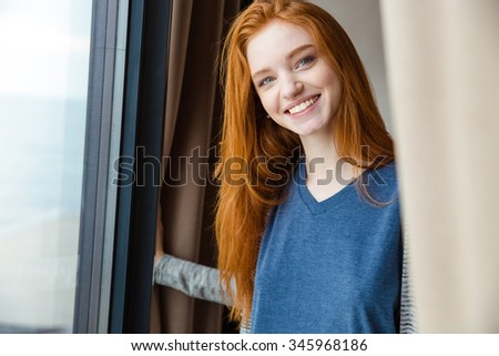 Cheerful content pretty girl with long red hair looking camera and smiling - stock photo