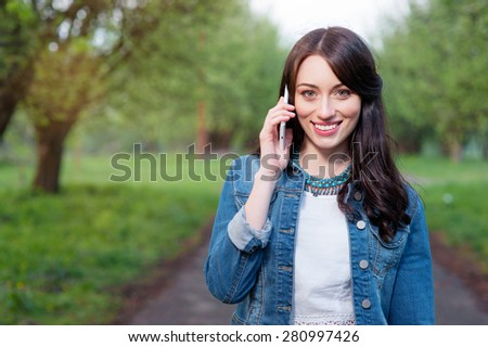 Cheerful conversation. Attractive young woman talking by smartphone while walking by summer park. - stock photo