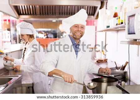 Cheerful cooks cooking at professional kitchen in the take-away  restaurant
